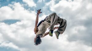 Male performing a back flip with clouds in the background