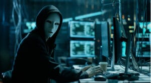 Masked person sitting behind pc screens in a dark lit setting