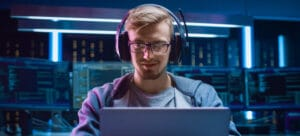 Male with gaming headphones smiling and sitting behind laptop